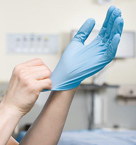Surgeon putting on glove